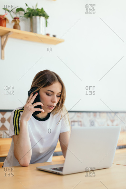 Young woman sitting at wooden table at a cafe working on laptop and talking on cell phone