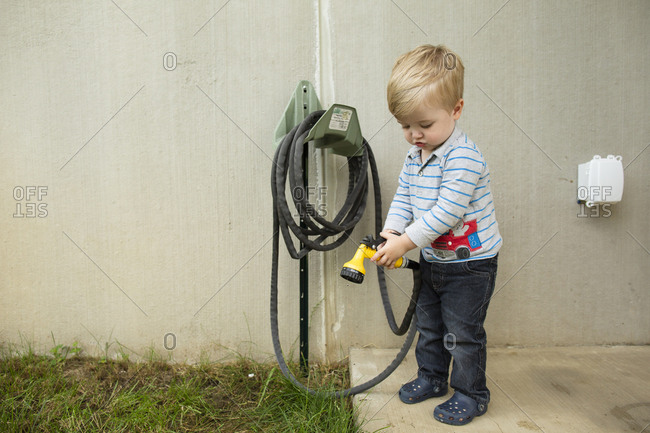 Cute toddler boy holds water hose to spray grass outside house
