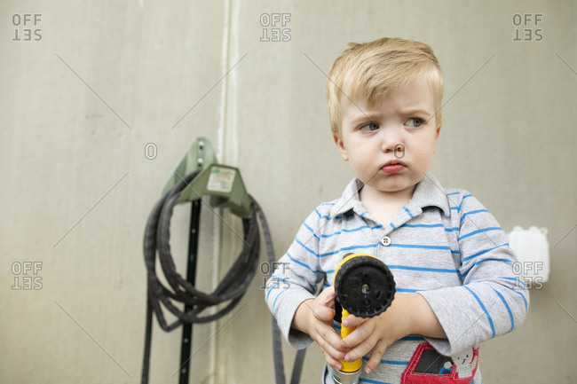 Upset toddler boy looks sideways while pouting and holding garden hose