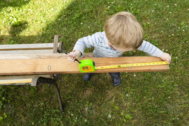 Overhead view of blonde toddler boy measuring a wooden board outside