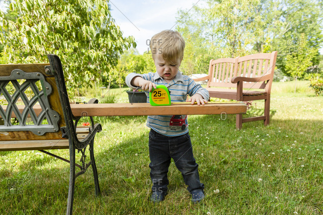 Toddler boy looks frustrated while measuring wooden board outdoors