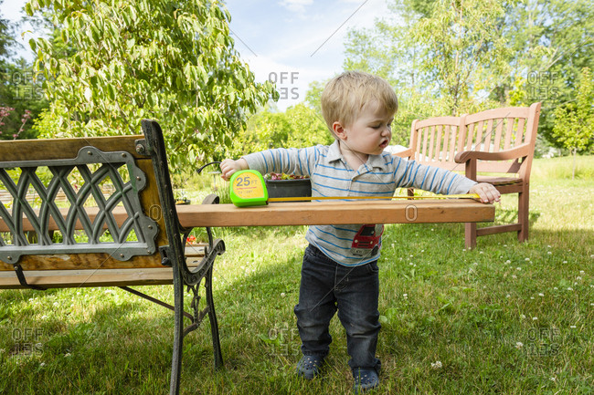Toddler boy looks serious as he measures a board outside in backyard