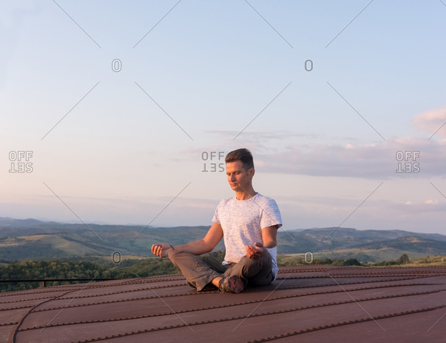 Adult man meditating on the terrace in the heat of the setting s