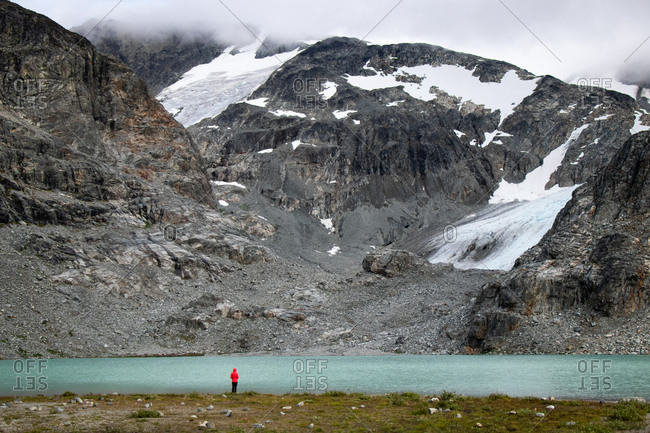 Hiker stands by lake against mountains and glacier