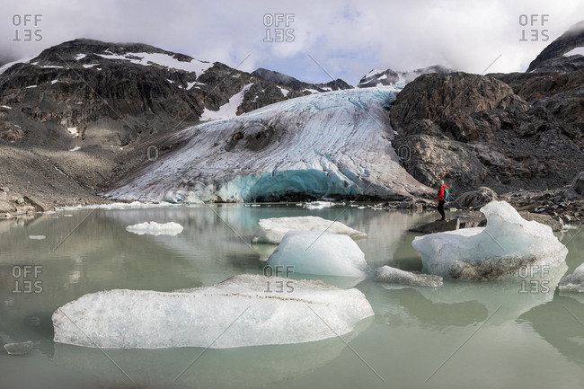 Side view of hiker by glacier and floating ice