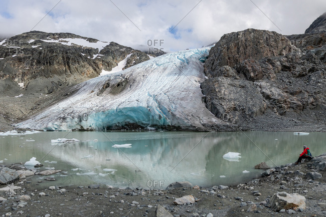 Side view of hiker sitting by lake and melting glacier