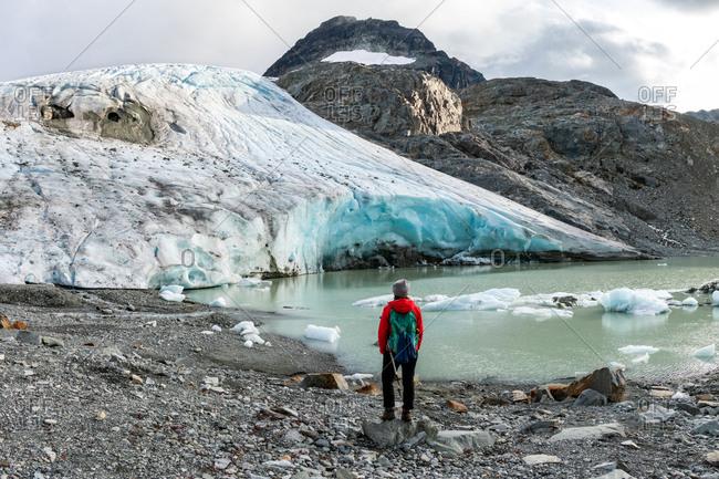 Rear view of hiker against melting glacier