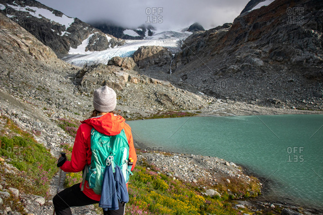 Rear view of hiker girl against glacier and mountain