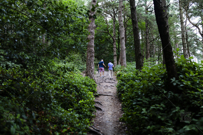 Man and Teen Boy Walking in Woods