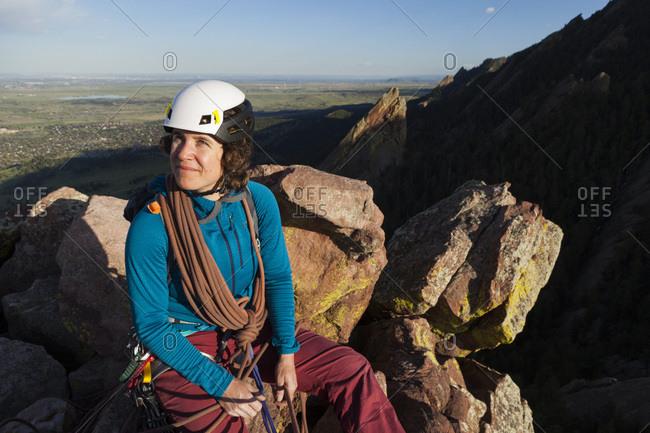 Woman rock climber on First Flatiron summit above Boulder, Colorado