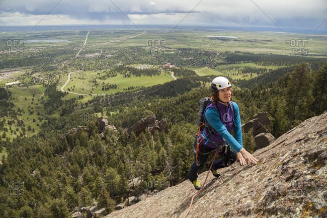 Woman rock climbs Fifth Flatiron as rain falls over Boulder, Colorado