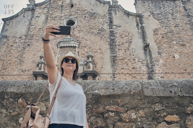 Tourist girl taking a selfie in front of an old stone church in