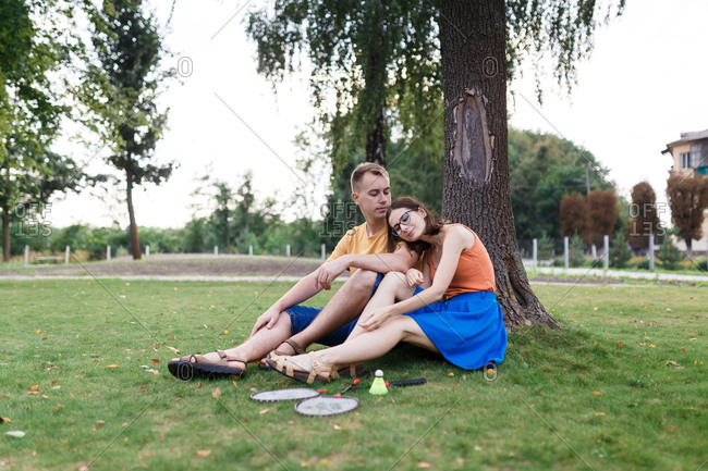 Millennial couple sitting in the grass after playing badminton in the park