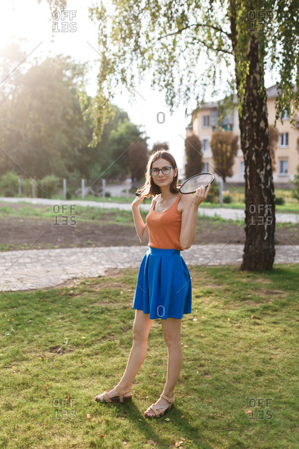 Portrait of millennial woman with badminton racket in a park
