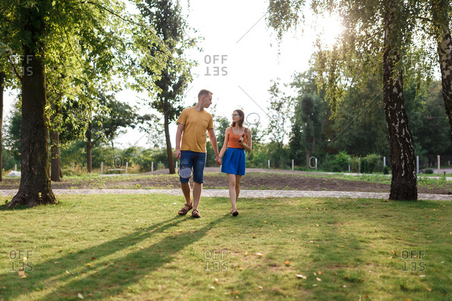 Young couple walking hand-in-hand to go play badminton in the park