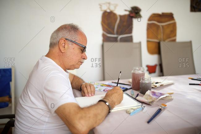 Senior man painting watercolor.