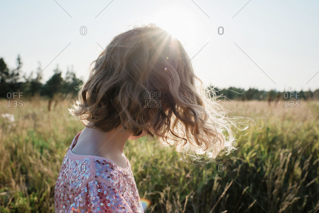 Portrait of the back of a girl walking at sunset in a sparkly dress