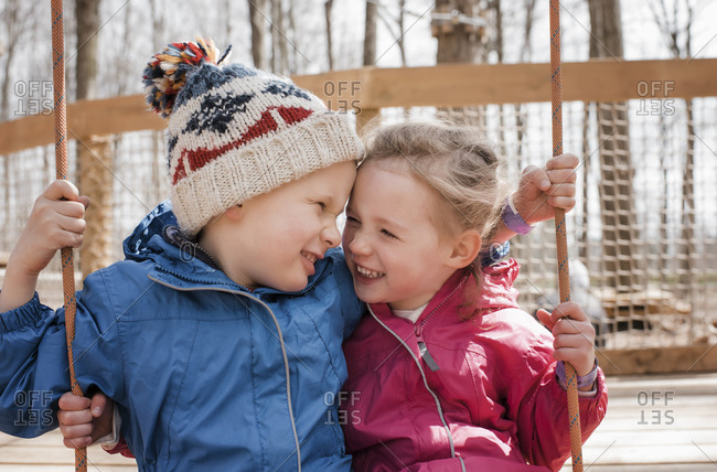 girl and boy on a swing together playing and laughing outside