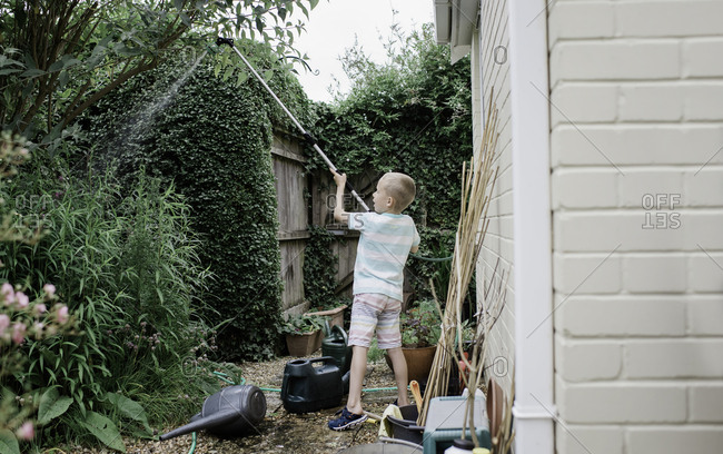 young boy watering his english country garden in summer