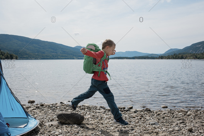 boy jumping on rocks with a backpack on camping by the sea