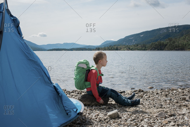 young boy camping sitting on a rock with a backpack and tent