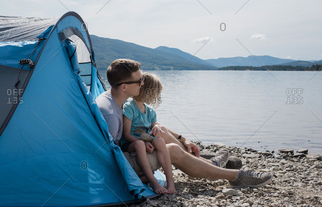 dad hugging his daughter whilst sat in a tent camping by the sea