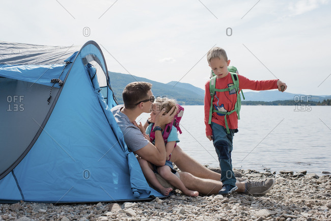 father kissing his daughter whilst his family plays camping by the sea