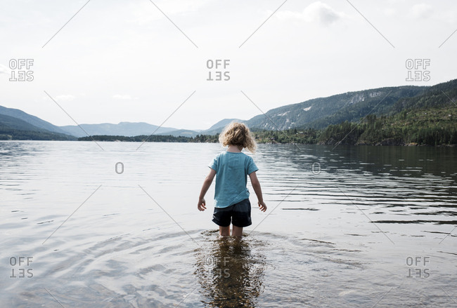 young blonde girl walking in the sea with wet clothes by the mountains