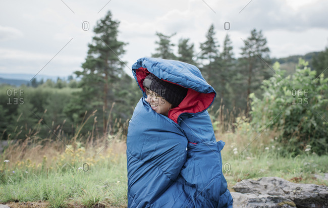 Portrait of a woman wrapped in a sleeping bag whilst camping outdoors