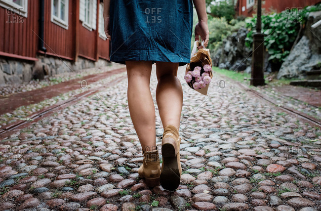 females legs walking on a cobbled street holding flowers