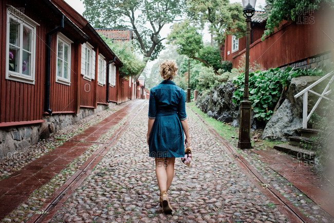 the back of a woman walking through a cobbled street with flowers