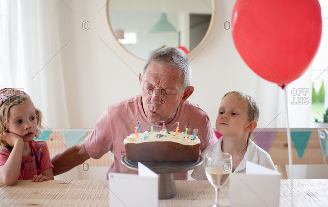 grandad sat with his grandchildren on his birthday blowing candles