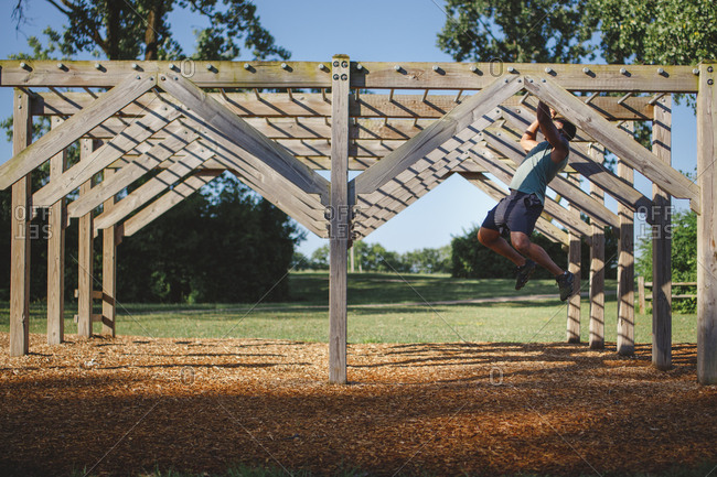 A strong man swings hangs from monkey bars in a park