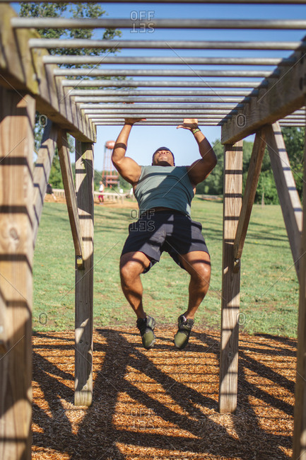 Front view of a strong man swinging across monkey bars in park