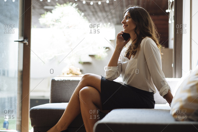 Brunette woman with office clothes talking on the phone on a couch.