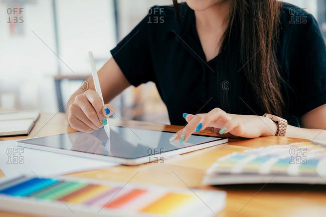 Graphic designer working at her desk in creative studio office.