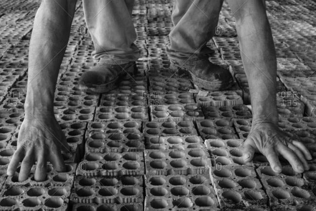 Worker picks bricks in a brick yard