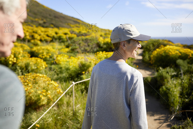 Senior couple walking on trail amidst plants against sky during summer