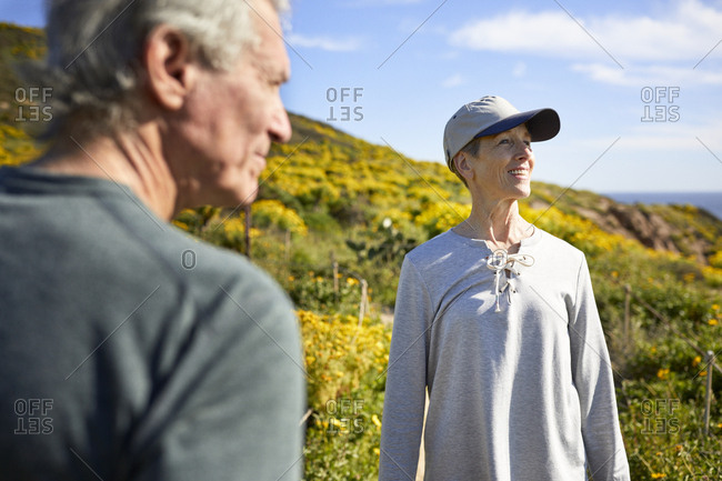 Senior couple looking away while standing on mountain against sky during sunny day