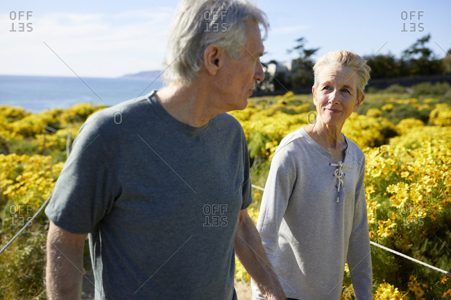 Senior couple looking at each other while walking on landscape during sunny day