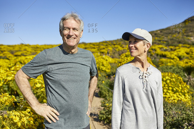 Smiling senior couple standing on mountain against blue sky during summer
