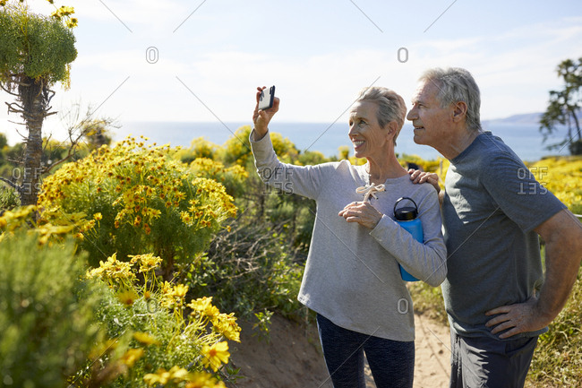 Smiling senior couple taking selfie through smart phone while standing on landscape by sea against sky during sunny day