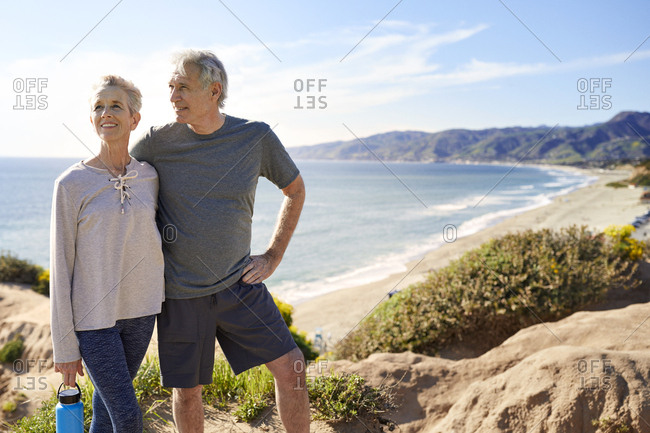 Smiling senior couple standing on cliff at beach against sky during sunny day