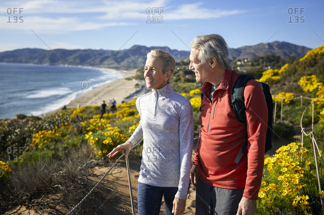 Smiling senior couple talking while walking on mountain by beach against sky during summer