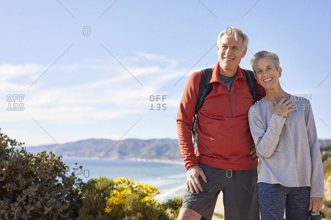 Cheerful senior couple standing against sky during sunny day