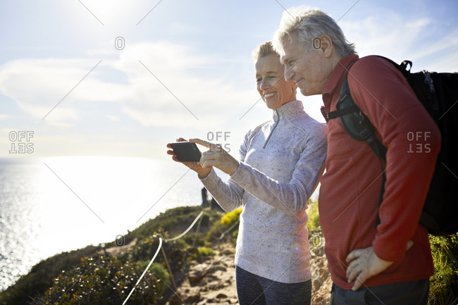 Smiling senior couple taking selfie while standing by sea against sky during sunny day