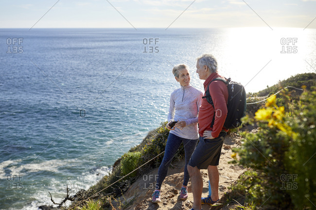 Full length smiling senior couple talking while standing on cliff by sea during sunny day