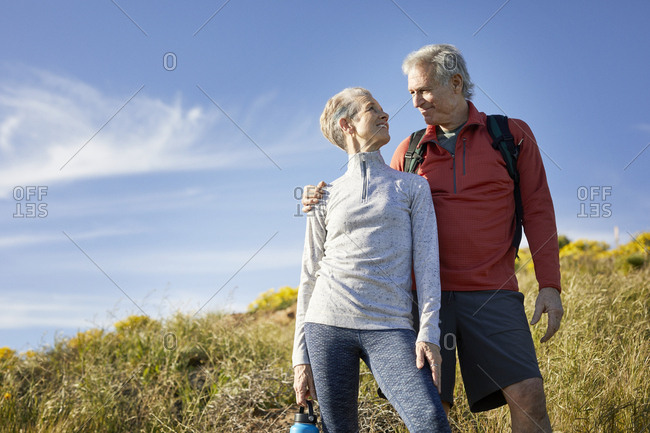 Low angle view of smiling senior couple looking at each other while standing on cliff against blue sky during sunny day