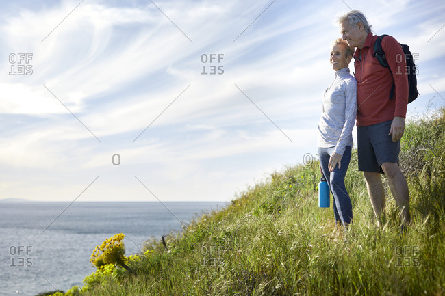 Smiling couple looking at sea while standing on cliff against sky