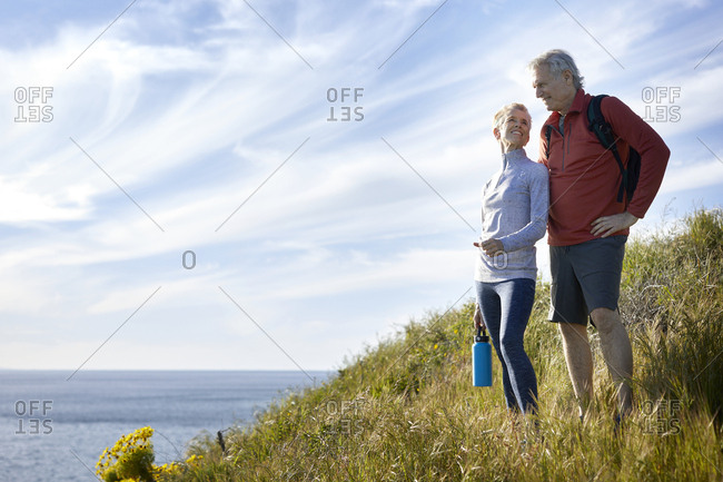 Smiling senior couple standing on cliff by sea against sky